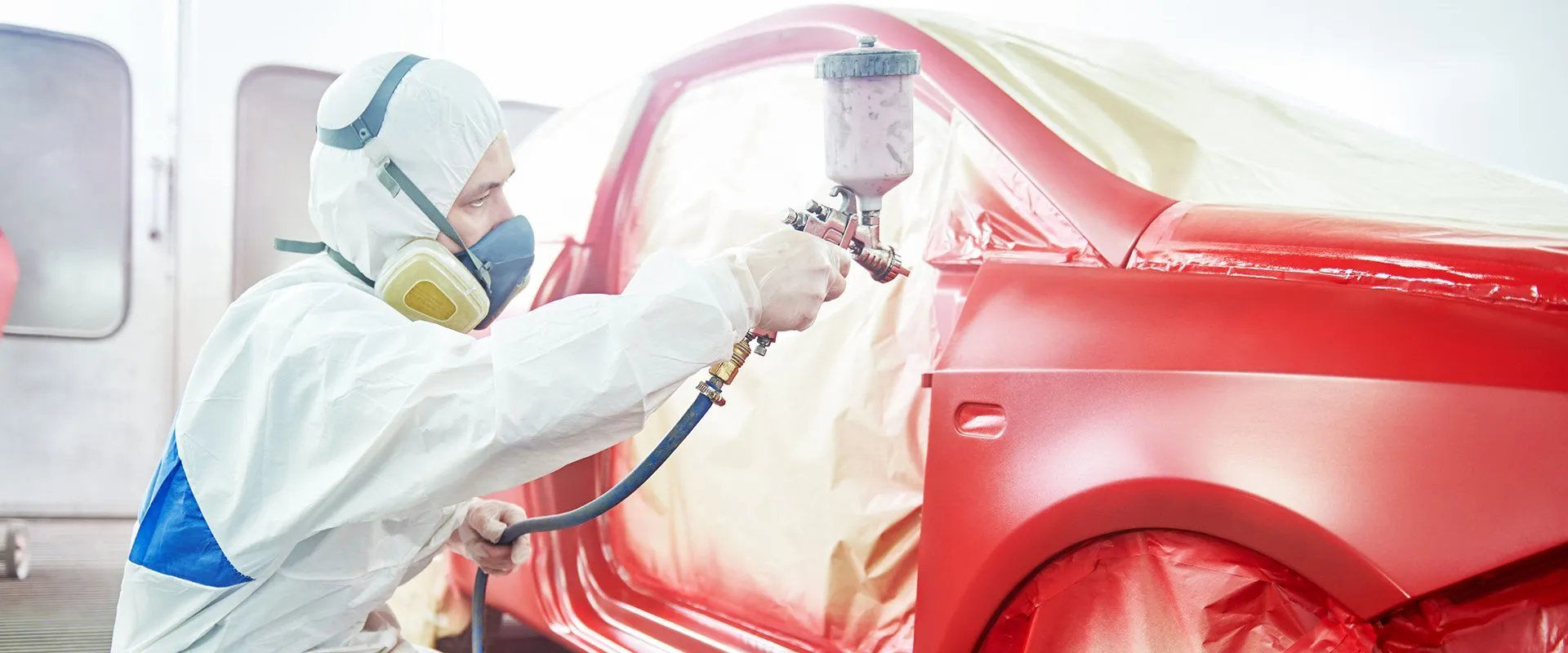 auto body technician painting a masked vehicle