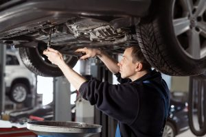 Handsome mechanic in uniform is working in auto service with lifted vehicle. Car repair and maintenance. Oil change