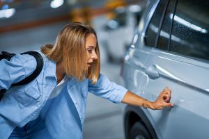 Woman looking at newly dented door on car